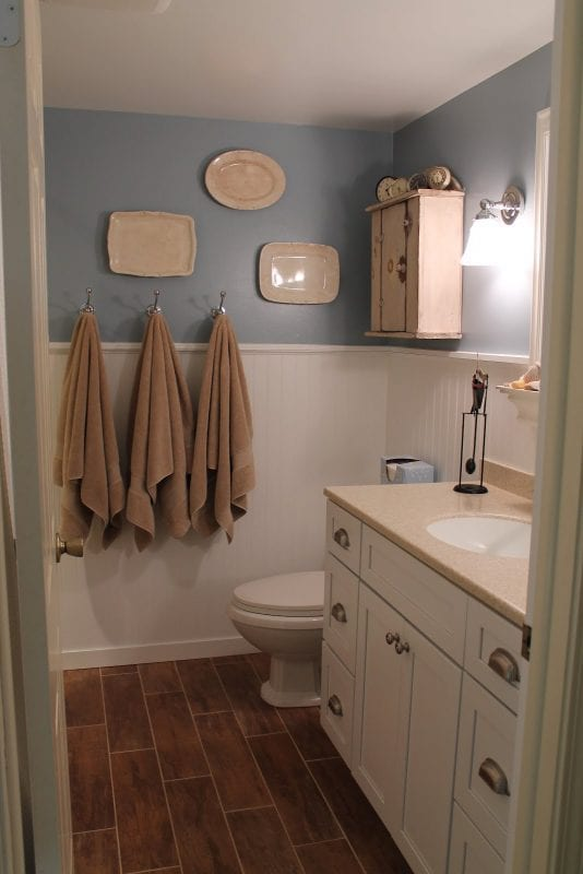1 Bathroom Remodel using woodgrain tile, by Elizabeth and Co featured on @Remodelaholic