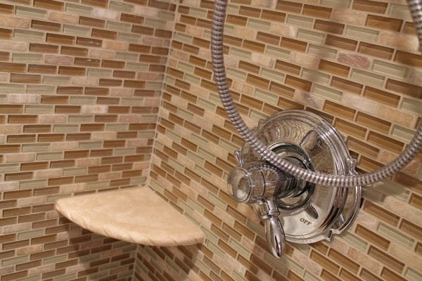 27 Shower makeover using mosiac glass and natural stone tiles, by Elizabeth and Co featured on @Remodelaholic