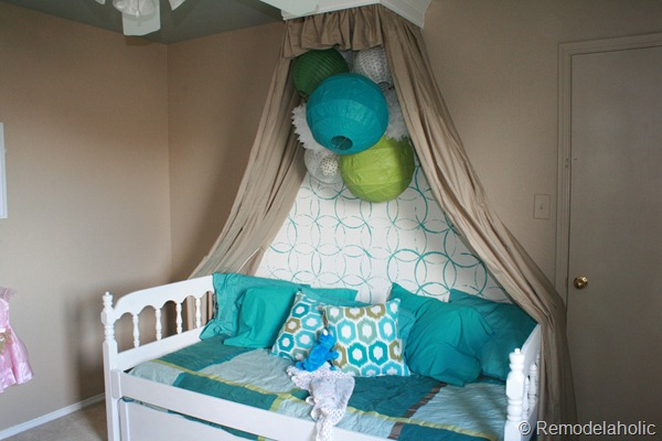 girls bedroom with stenciled wall and crown cornice canopy bed blue
