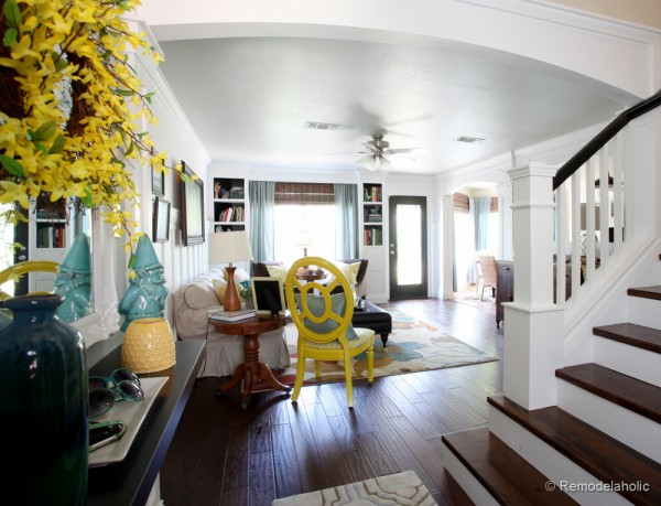 Living Room Remodel with yellow accents wood floors and built-in bookcases and columns with arches-3