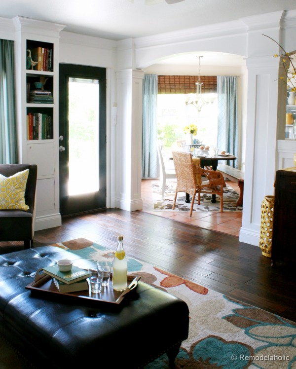 Living Room Remodel with yellow accents wood floors and built-in bookcases and columns with arches-35