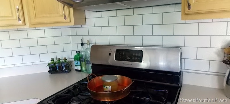 stove with faux painted subway tile backsplash