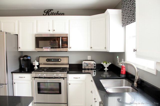 Black and white kitchen remodel with painted cabinets for Spraying kitchen cabinets white