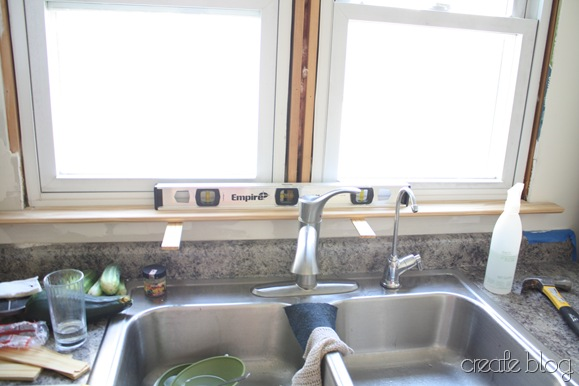 trimming the windows in our white kitchen remodel