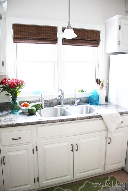 white kitchen with granite counter and stainless steel sink