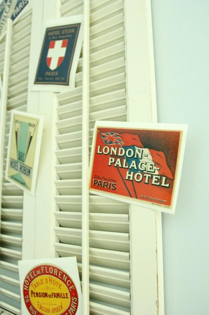 travel postcard shutter display above antique trunk bookshelf, featured on Remodelaholic.com
