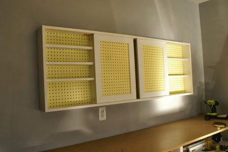 wall-mounted pegboard tool cabinet with sliding doors, tutorial featured on Remodelaholic.com