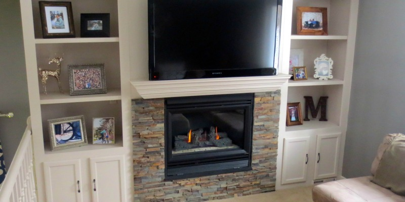 Reclaim some mantel style by renovating the fireplace! See this lovely fireplace makeover with built-in shelves and lovely stone tile.
