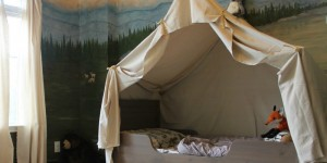 feature woodland themed kids room with camping tent bed and play campfire, The Ragged Wren on Remodelaholic