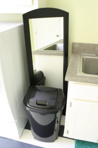 use a tall mirror to hide laundry room plumbing fixtures, featured on Remodelaholic