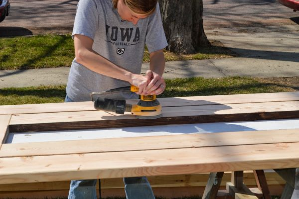 sanding an outdoor dining table made from inexpensive pine