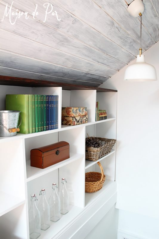 Whitewashed attic ceiling with built-in shelving along stairs - Maison de Pax on Remodelaholic.com