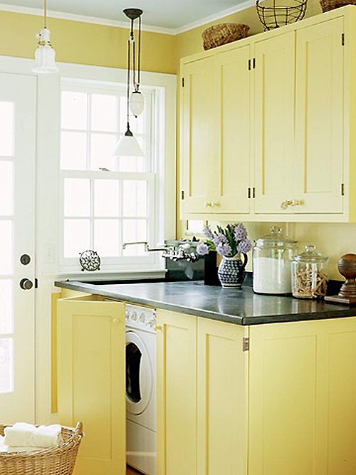 Built in Laundry room in Mudroom with yellow cabinets featured on remodelaholilc.com
