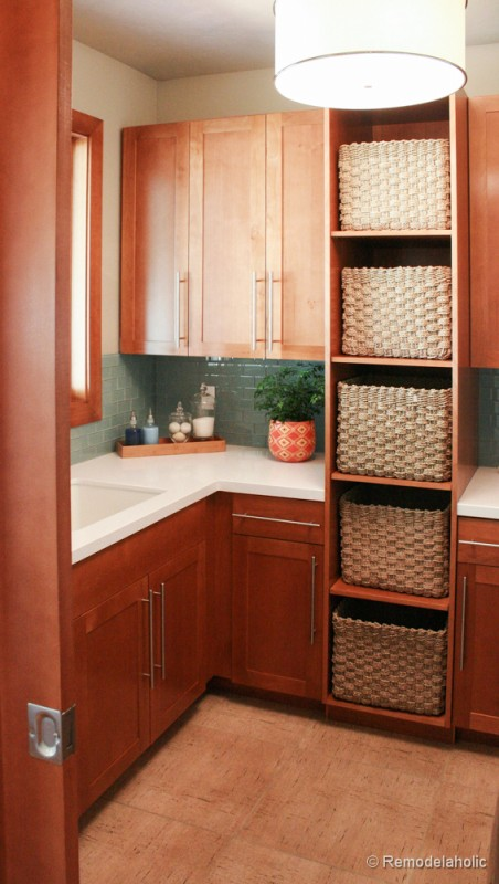 Shelves with basket storage in the laundry room. Fabulous Laundry room design ideas from @Remodelaholic