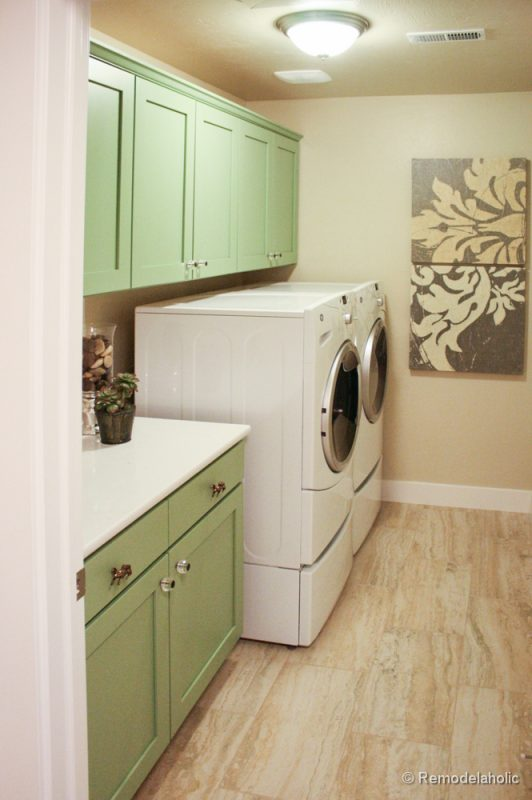 Pretty Green Cabinets in a one wall laundry room. Fabulous Laundry room design ideas from @Remodelaholic