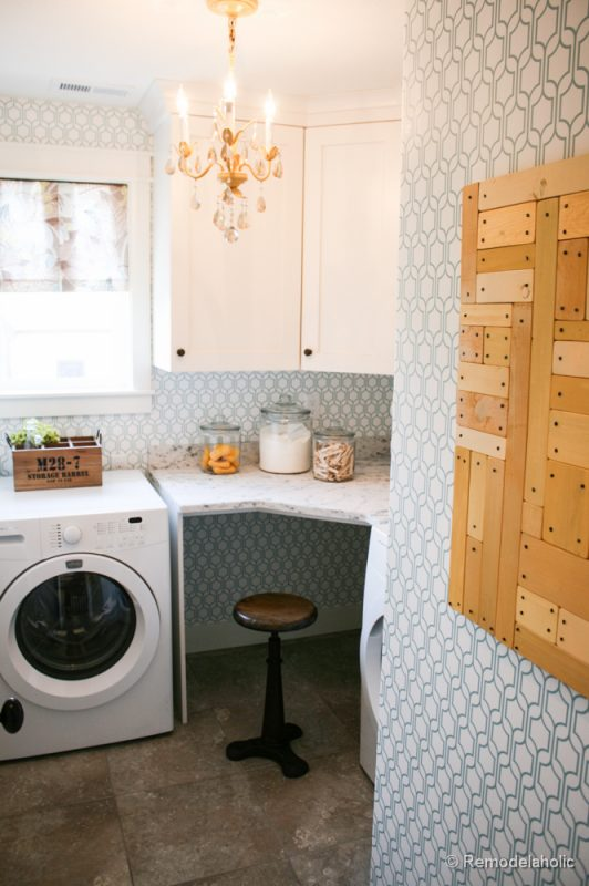 Beautiful wallpapered glam laundry room with small desk spot. Fabulous Laundry room design ideas from @Remodelaholic