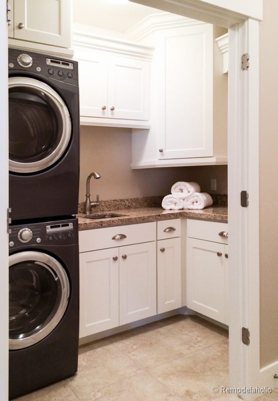 Small laundry room with a sink and lots of storage with cabinets from floor to ceiling. Fabulous Laundry room design ideas from @Remodelaholic