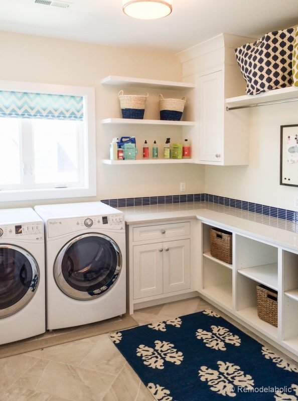 White and blue laundry room with lots of shelf storage. Fabulous Laundry room design ideas from @Remodelaholic