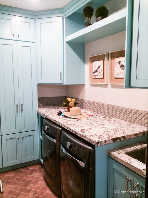 Blue cabinets and brick floor for a unique laundry area. Fabulous Laundry room design ideas from @Remodelaholic