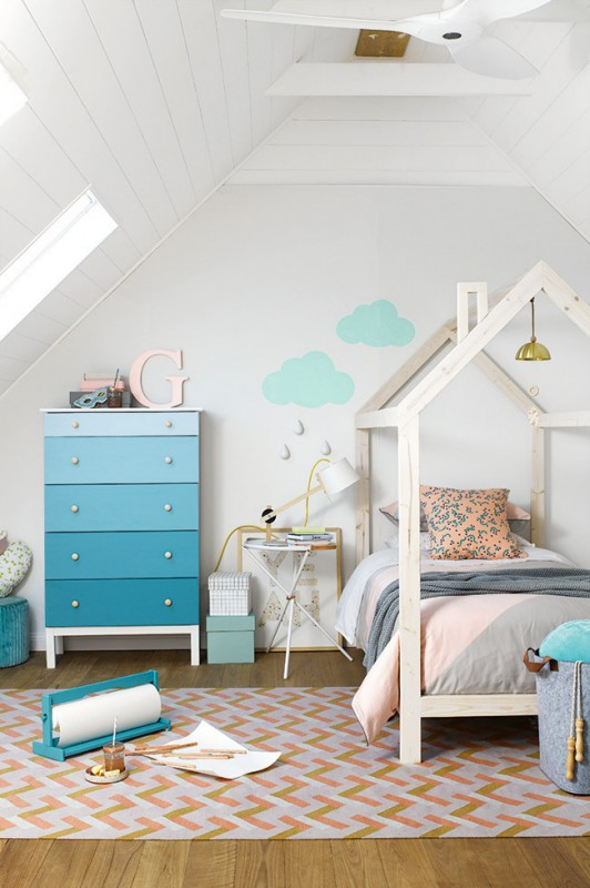 Kids room with house bed frame, blue ombre dresser, geometric rug, and cloud wall decals