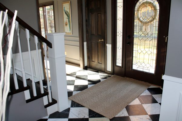 entry with checkered tile and curved staircase remodel - Construction2Style via @Remodelaholic