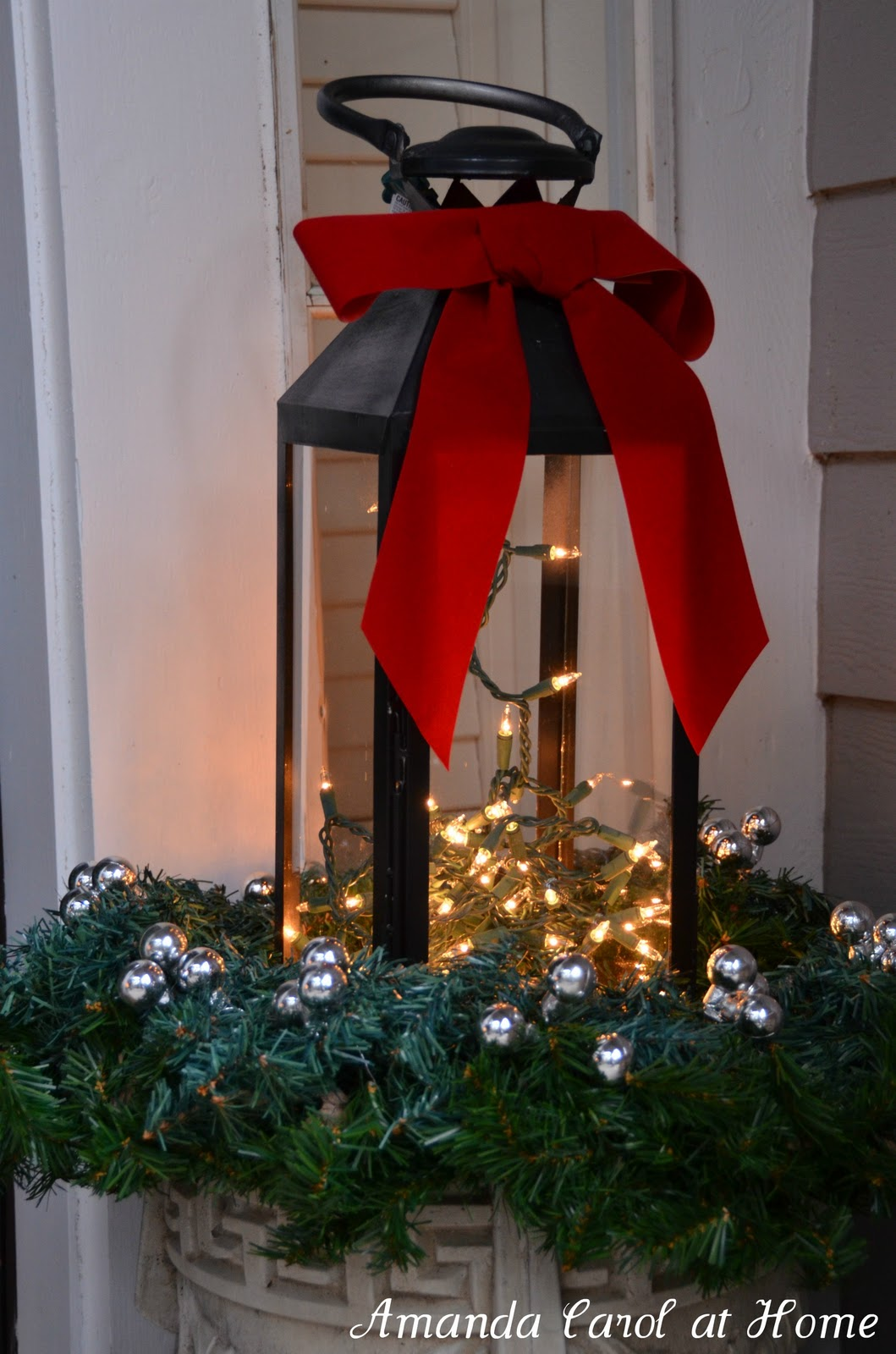 Christmas window box filler - Lantern In Outdoor Planter For Winter Amanda Carol At Home Via Remodelaholic