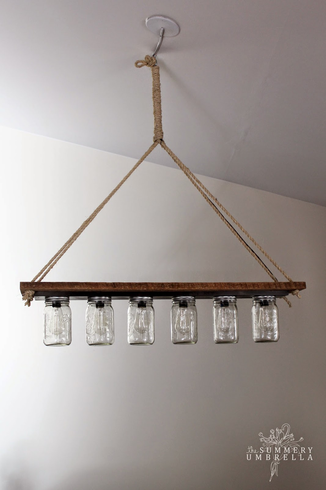 Simple mason jar chandelier with edison bulbs made from a hollywood style lighting strip The