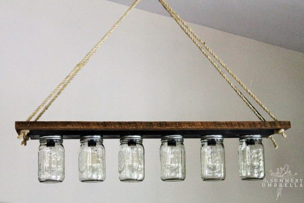 mason jar pendant chandelier light from bathroom vanity light strip - The Summery Umbrella featured on @Remodelaholic