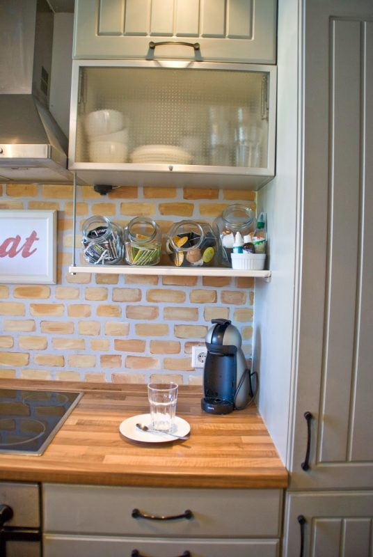 open shelf beneath cabinets with brick backsplash and butcherblock countertops - Pudel-design featured on @Remodelaholic