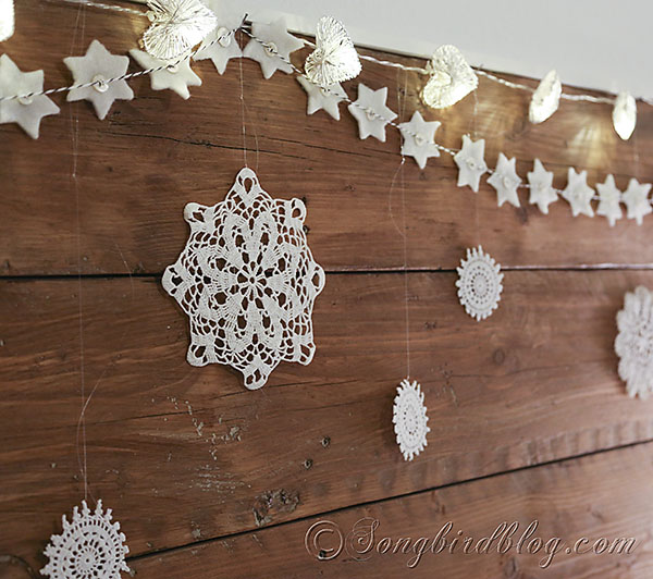use a winter garland on the headboard to decorate a bedroom for christmas songbird blog