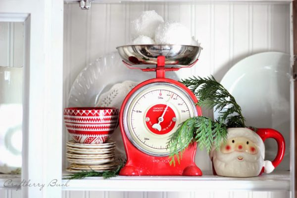 use evergreen and red to decorate a hutch for Christmas - Craftberry Bush via @Remodelaholic