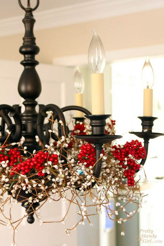wrap holly berry and pine garlands around the chandelier - Pretty Handy Girl via @Remodelaholic