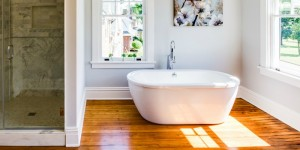 feature spacious open bathroom with wood floor, walk in marble shower, and white basin tub @Remodelaholic