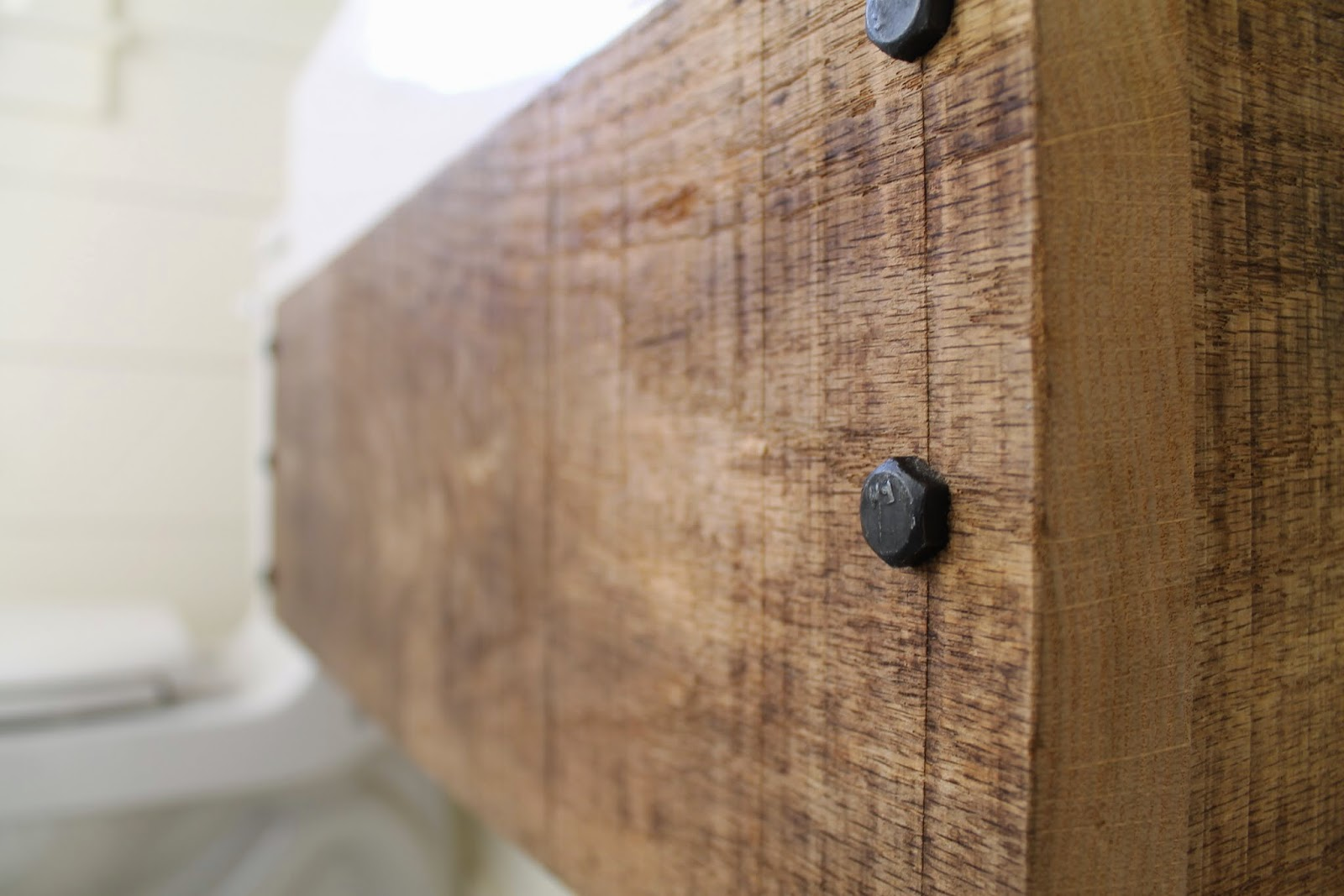 Fancy lag bolts for an industrial style floating reclaimed wood vanity Girl Meets Carpenter featured on