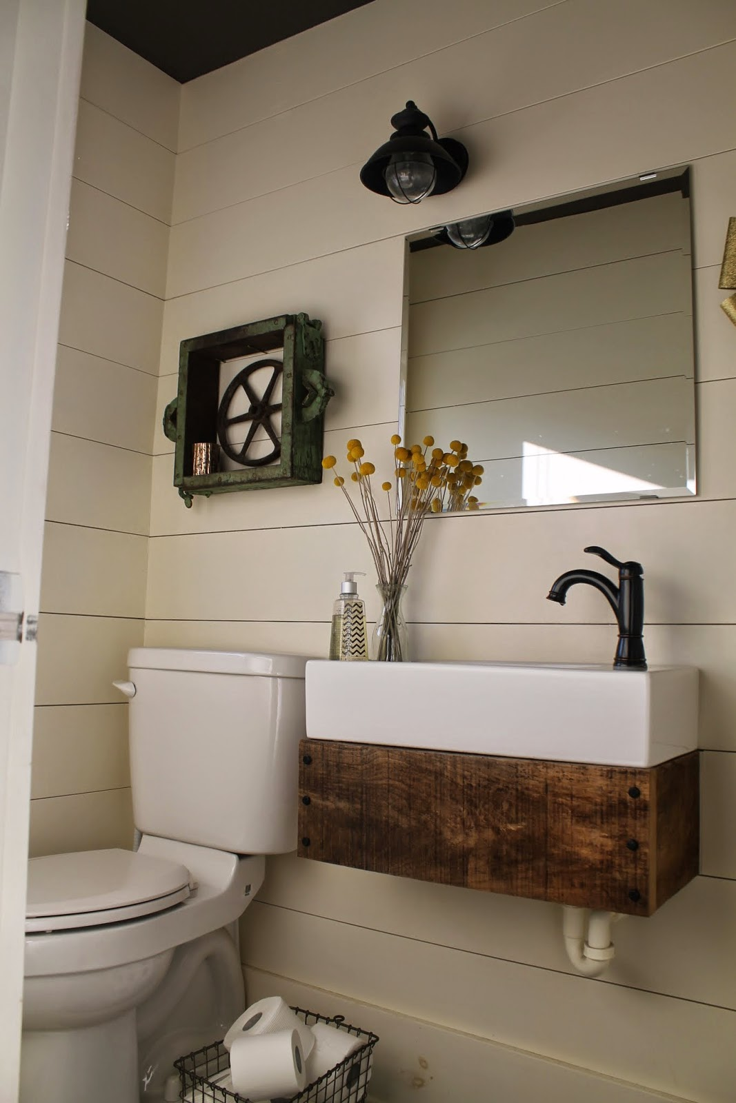 Stunning rustic reclaimed wood floating vanity in bathroom with planked walls Girl Meets Carpenter featured on