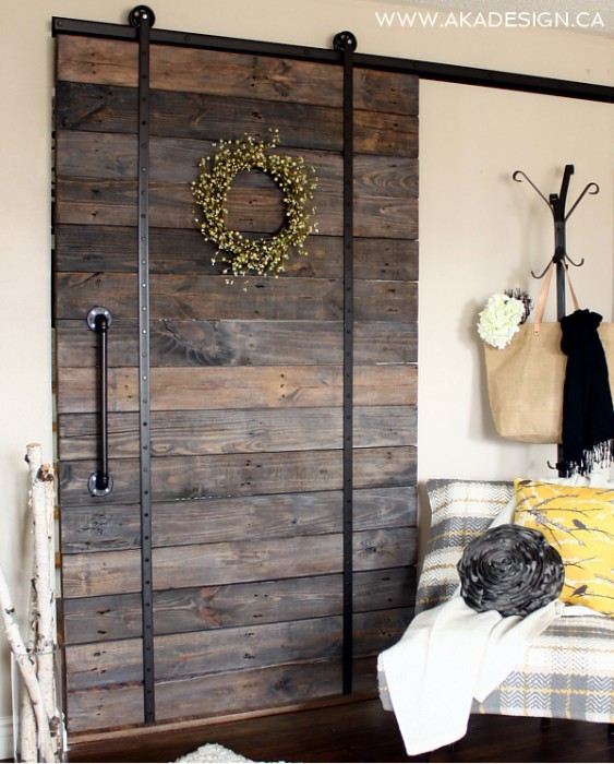 upcycled barn door using broken scooter wheels for hanging hardware - AKA Design