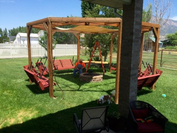 DIY round pergola with swings, firepit and shade screen featured on @Remodelaholic