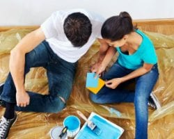 overhead view of couple having fun renovating their new home together with blue paint on a roller