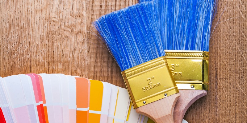paintbrushes  and color  palette on brown wooden board with copyspace