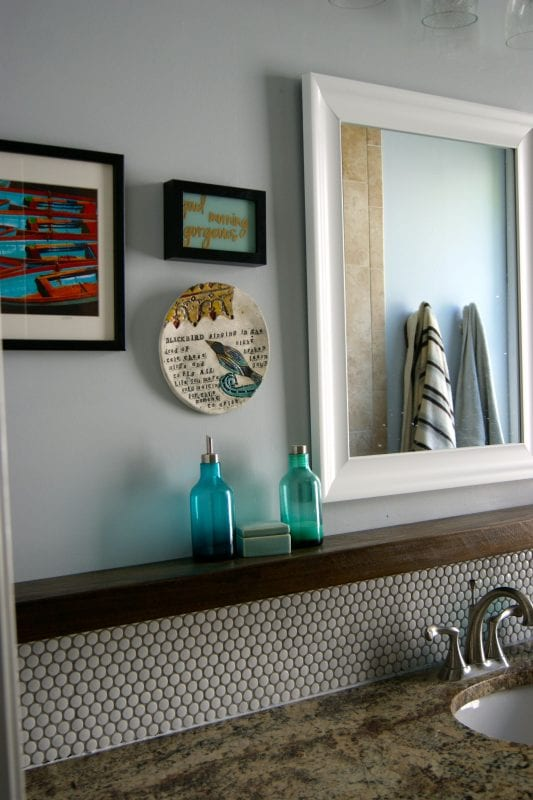 penny tile bathroom backsplash with floating wood shelf