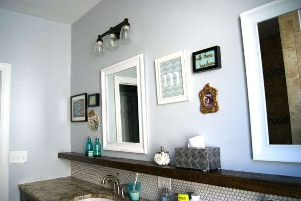 DIY bathroom makeover, framed white mirrors, floating wood shelf, penny tile, painted gray