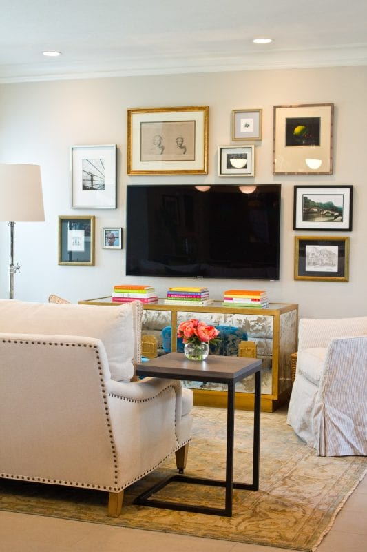 balanced gallery wall with gold frames around TV (via Material Girls)