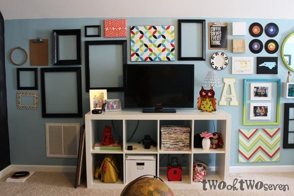 television as part of a long gallery wall in a family room - use empty frames and other elements (via twoohtwoseven)