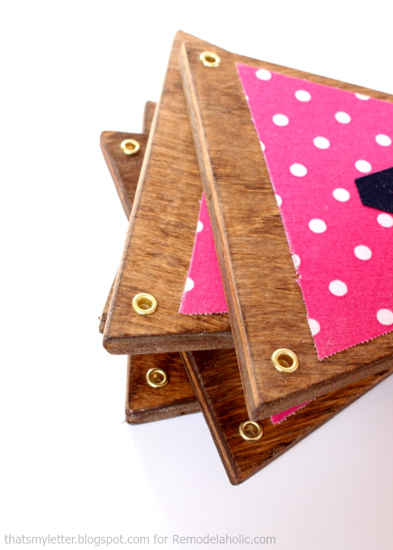use metal grommets on triangles of scrap wood to make a cute fabric and wood bunting