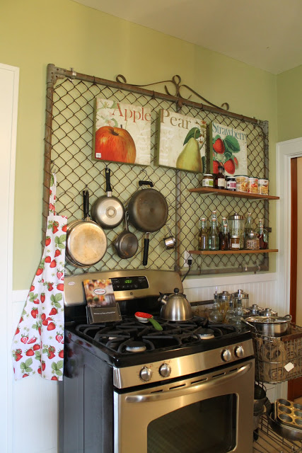 kitchen organized wall using an old gate to hang pans and spices
