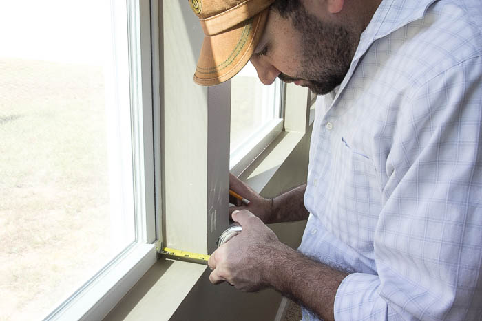 Measuring to cut perfectly for DIY window trim featured on Remodelaholic.com