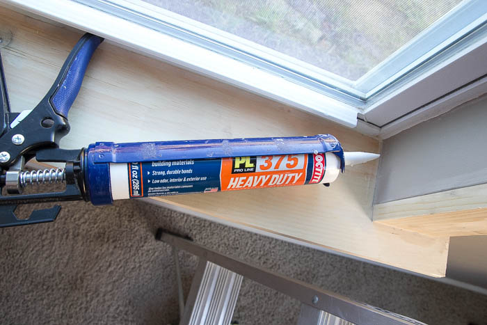 Caulking after installing DIY window trim featured on Remodelaholic.com