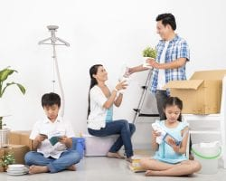 Vietnamese family unpacking cardboard boxes in their new house