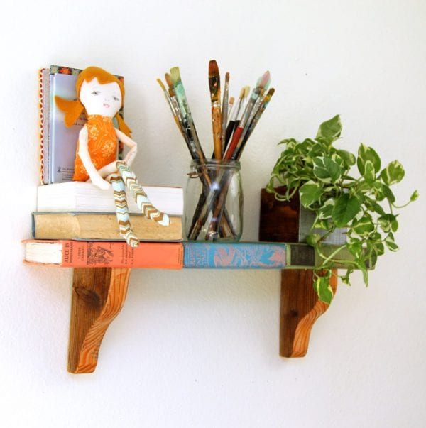 "This easy DIY ""book""shelf is great for a book enthusiast or vintage collector! Repurpose old books into a unique DIY wall shelf, plus use our free printable book covers so you don't actually have to use rare vintage books."
