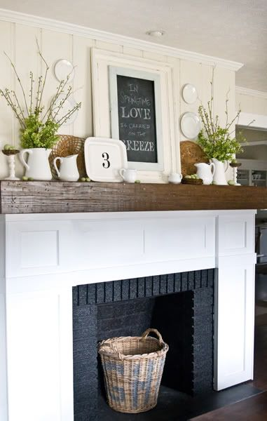 Gorgeous layered mantel arrangement with white dishes and a chalkboard
